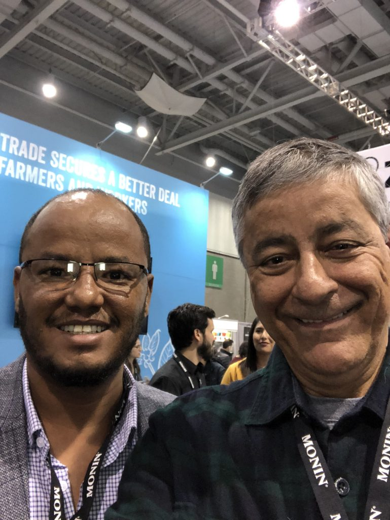 Getahun Gebrkidan of Eastern & Central Africa Fairtrade Network, and Jairo Blanco of Logical Machines, in the Fairtrade Network booth during the 2019 Specialty Coffee Expo in Boston